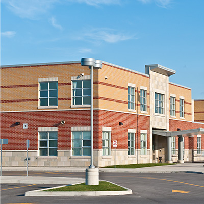 DC Byers is one of the leading concrete restoration contractors in Michigan. From masonry projects on hundred year old buildings, to schools and parking ramps, we get the job done. The exterior of a school parking lot.