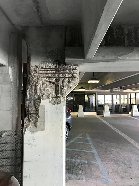 Concrete restoration is needed when you see exposed rebar, like this support column in a parking lot ramp.
