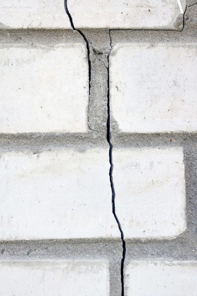A long crack forms along a white brick facade.
