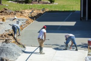 A DC Byers crew can add driveway maintenance to our services if your project is in a heavy trafficked area. Workers pour concrete for an extra wide driveway.